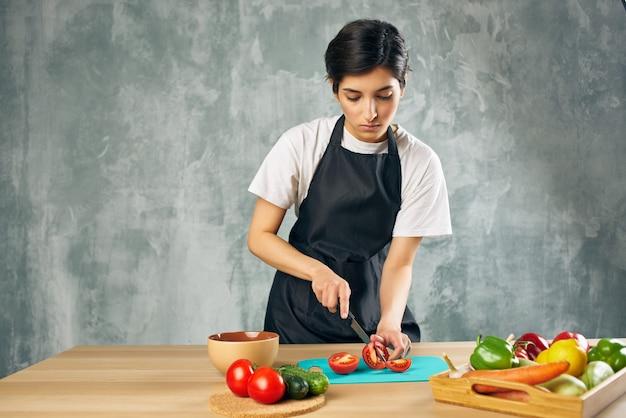 Женщина в черном фартуке на кухне режет овощной салат, диета