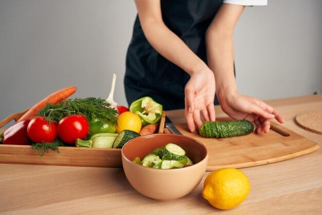 黒エプロンスライス野菜キッチン調理食品の女性