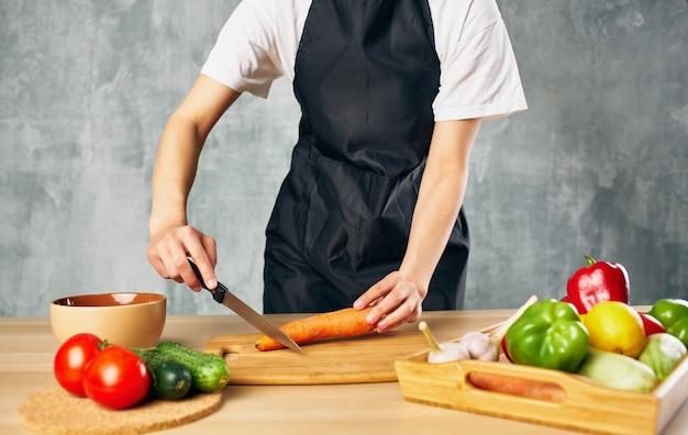 生鮮食品を調理する野菜キッチンをスライスする黒いエプロンの女性。