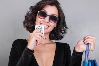 Woman in black biting credit card
