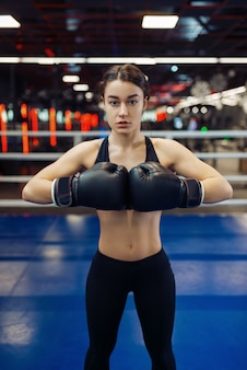 黒のボクシンググローブをはめた女性が手を差し出し、正面図、リングでのボックストレーニング。ジムの女性ボクサー、スポーツクラブの女の子キックボクサー、パンチ練習