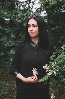 Женщина в черной одежде держит в руке белый цветок на фоне зеленых листьев