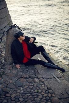 黒い服のジャケットのズボンの帽子と赤いシャツの女性は秋の川の近くに座っています