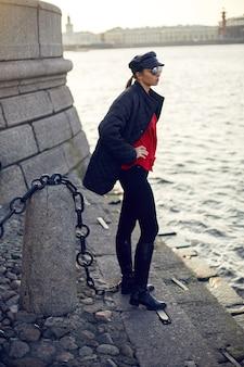 黒い服のジャケットのズボンの帽子と赤いシャツを着た女性が川の近くの石の上に立っています