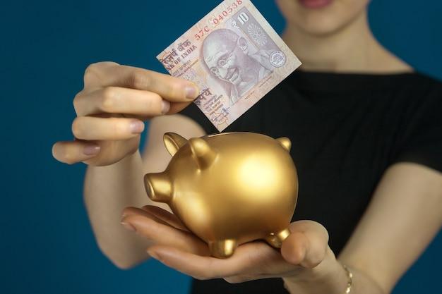 Женщина в черной одежде с индийской рупией и копилкой в руках.