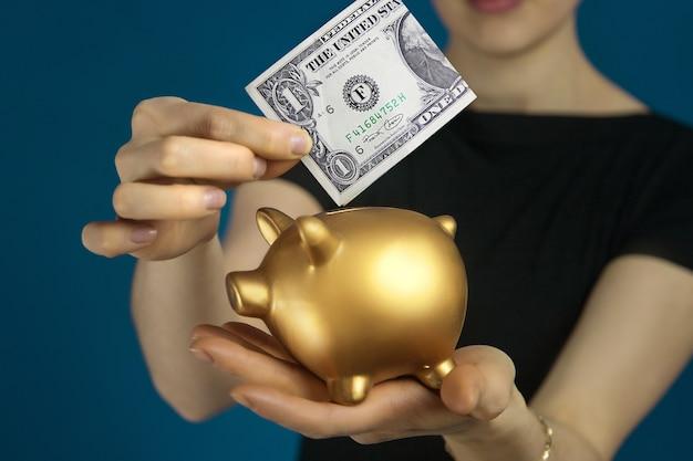 Женщина в черной одежде с долларом сша и золотой копилкой в руках.