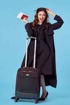 黒いコートの荷物空港旅行青い背景出張の女性