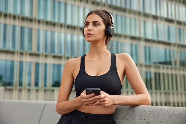 黒くトリミングされたトップの女性は、ソーシャルメディアでヘッドフォンチャットで曲を楽しんでいます朝のトレーニングは街の通りで携帯電話を閲覧し、オンラインラジオを聴きます