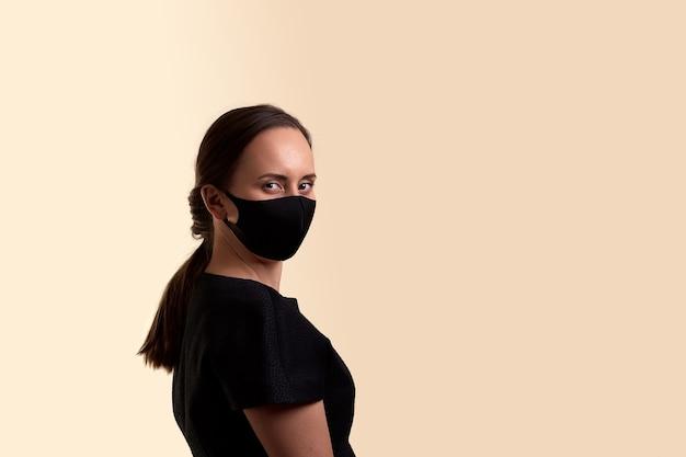 黒のドレスと黒のフェイスマスクを肩にかけた女性がベージュの壁を半回転