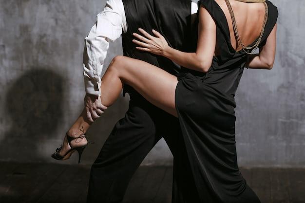 Женщина в черном платье и мужчина танцуют танго