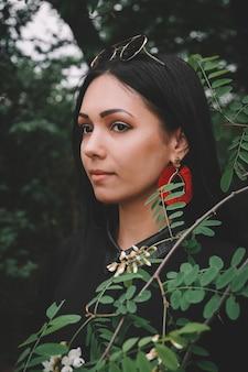 森を背景に小枝を手に持つ黒いドレスと赤い装飾の女性