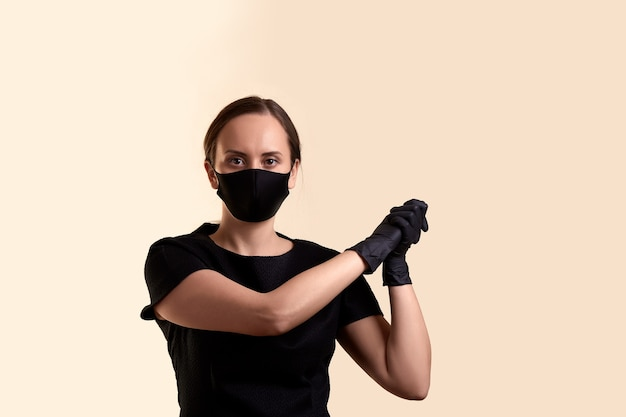 黒のドレスのフェイスマスクと手袋の女性は、側面とベージュの壁の上の拳で手を結合しました