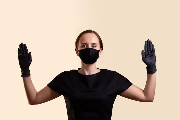 黒のドレスのフェイスマスクと手袋をはめた女性が手を上げて、ベージュの壁には何もないことを示しました