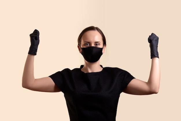黒のドレスのフェイスマスクと手袋の女性は、拳とベージュの壁を越えて手を上げた