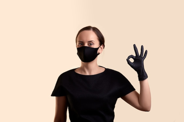 黒のドレスのフェイスマスクと手袋の女性は、okのシンボルとベージュの壁を示しています