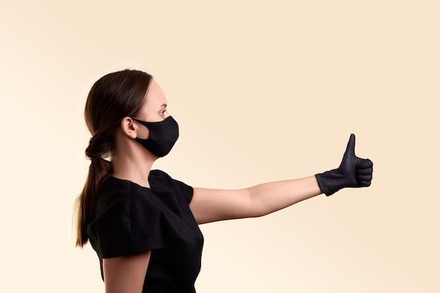 黒のドレスのフェイスマスクと手袋の女性がベージュの壁を横に親指を示しています