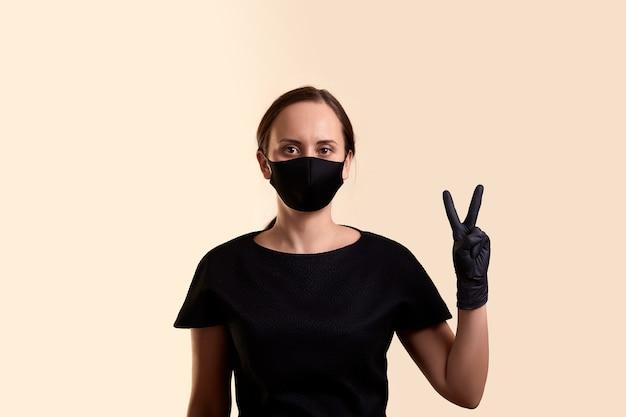 勝利の手とベージュの壁を示す黒いドレスのフェイスマスクと手袋の女性
