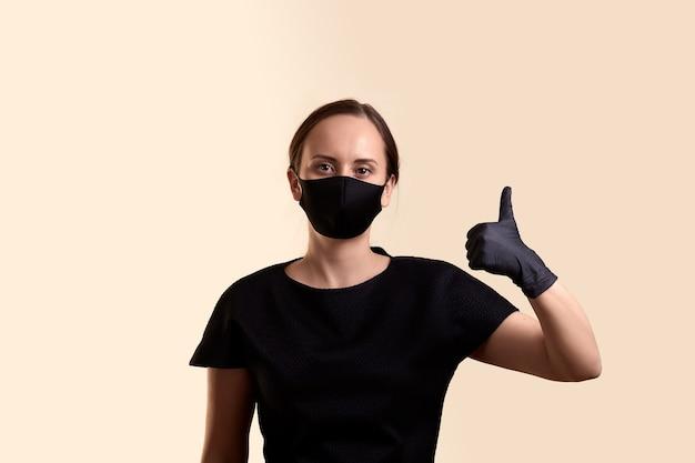 ベージュの壁の上にvthumbを示す黒いドレスのフェイスマスクと手袋の女性