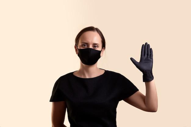 黒のドレスのフェイスマスクと手袋の女性は、挨拶として、ベージュの壁の上に手のひらを示しています