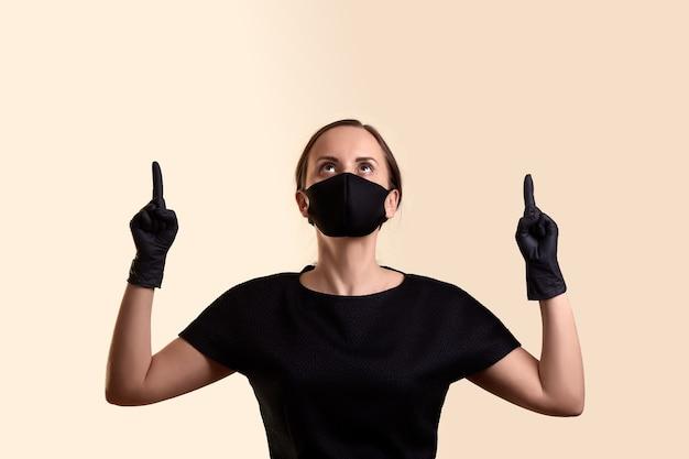 黒のドレスのフェイスマスクと手袋の女性は、ベージュの壁の上に人差し指を示しています