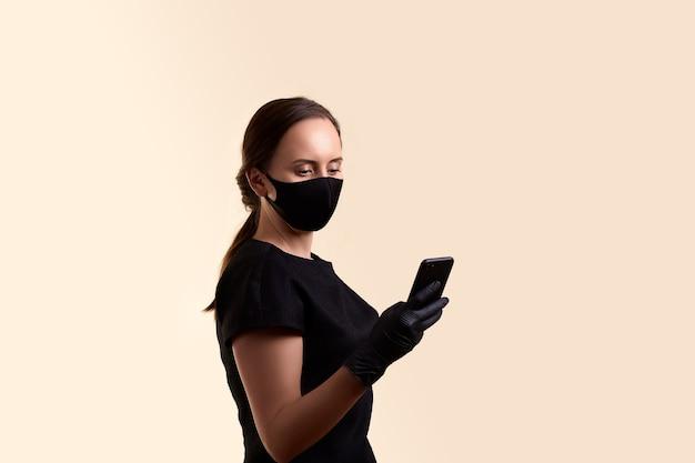 ベージュの壁に携帯電話を保持している黒いドレスのフェイスマスクとラテックス手袋の女性