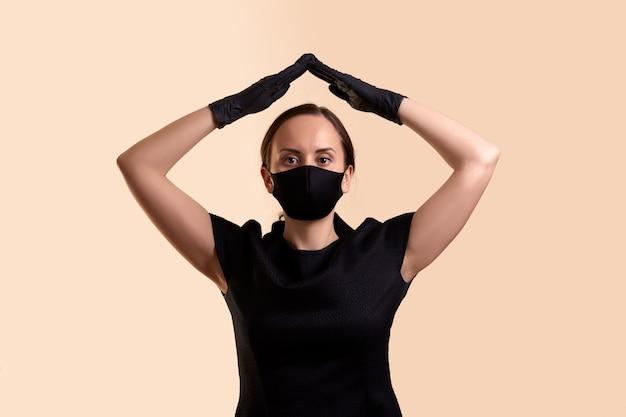 彼女の頭の上に両手を保持し、ベージュの壁の上に屋根を作る黒いドレスのフェイスマスクとラテックス手袋の女性