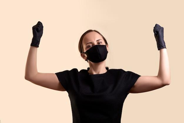 黒のドレスのフェイスマスクとラテックス手袋をはめた女性が拳で手を上げ、頭を下げてベージュの壁を越えた