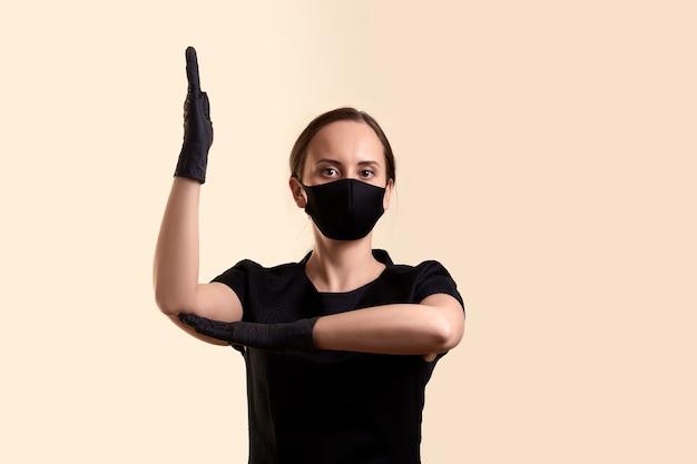 黒のドレスフェイスマスクとラテックス手袋を着用した女性は、学校のようにベージュの壁を越えて手を上げました