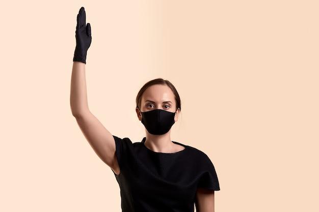 黒のドレスフェイスマスクとラテックス手袋をはめた女性が、議決権を要求するように、ベージュの壁を越えて手を上げた