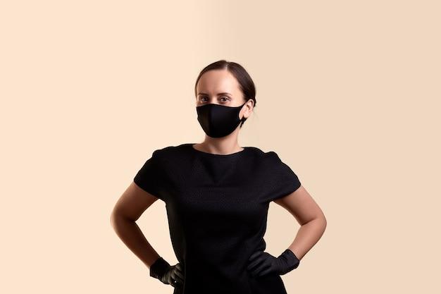 黒のドレスのフェイスマスクとラテックス手袋を着用した女性は、腕を腰に当ててベージュの壁の上に立っていることを誇示します