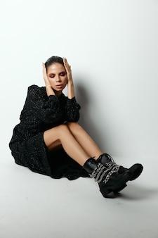 Женщина в черном платье модные ботинки модели студии. фото высокого качества