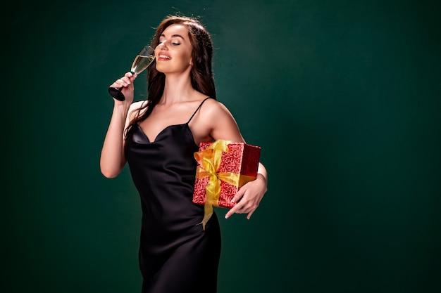 검은 드레스를 입은 여성이 빨간색 선물 상자와 샴페인 파티 시간 휴가 컨셉의 유리를 들고 있습니다.