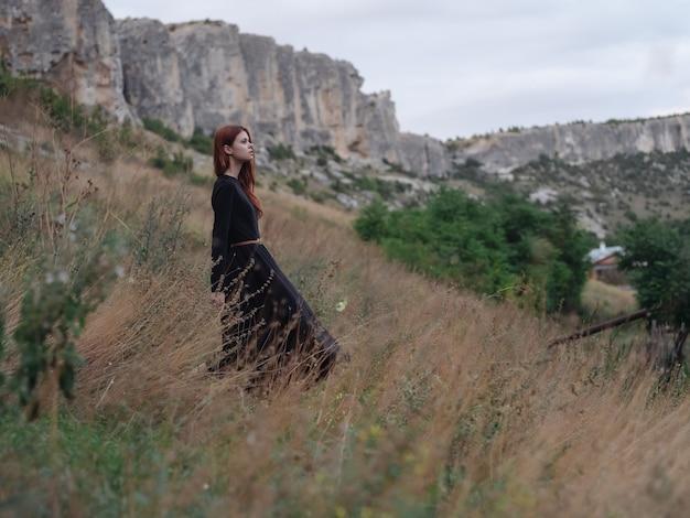 山の旅の散歩風景の黒のドレスを着た女性。高品質の写真