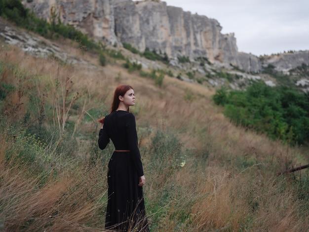 黒いドレスの山の女性は風景旅行を歩きます