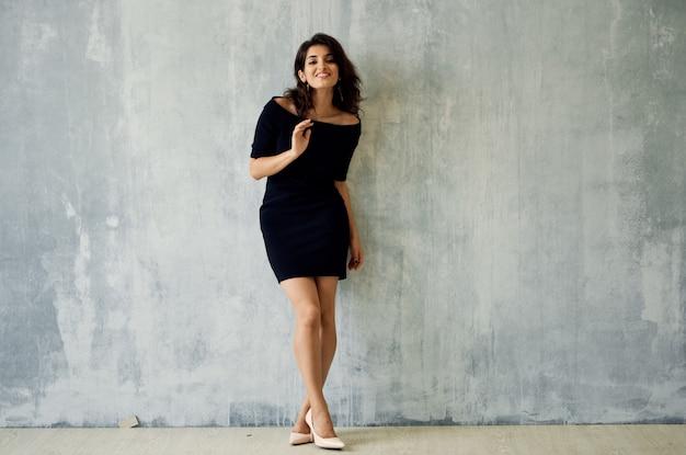 Женщина в черном платье у стены позирует моды