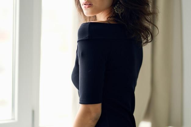 ファッションの贅沢なポーズをとる窓の近くの黒いドレスの女性
