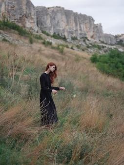 秋の牧草地の山の屋外で黒のドレスを着た女性