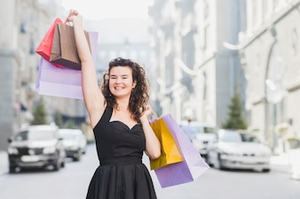 Woman in black dress raising her arms with colorful shopping bags