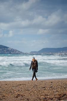 昼間にサインビーチの前に立っている黒いドレスの女