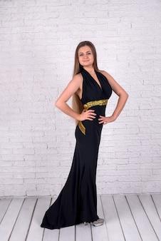 白いレンガの壁に黒いドレスを着た女性