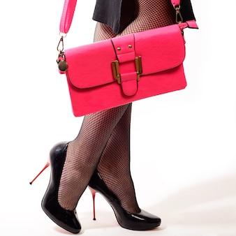 Женщина в черном платье в туфлях на красных высоких каблуках и держит розовую сумочку