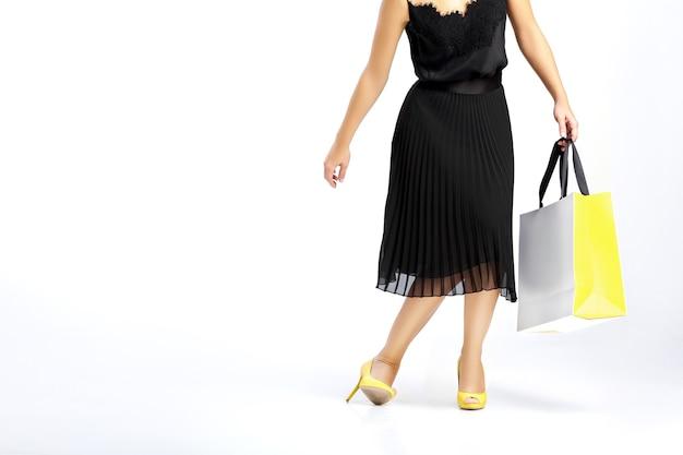 흰색 바탕에 쇼핑백과 검은 드레스에 여자.