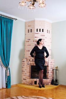 블랙 이브닝 드레스에 여자입니다. 벽난로가있는 인테리어