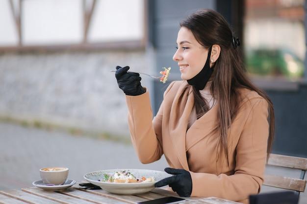カフェに座ってビーガンサラダを食べる準備をしている黒いフェイスマスクの女性。検疫カフェのコンセプト。 covid19。