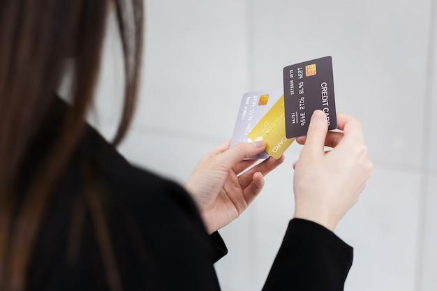 Женщина в черном строгом костюме держит в руках кредитные карты