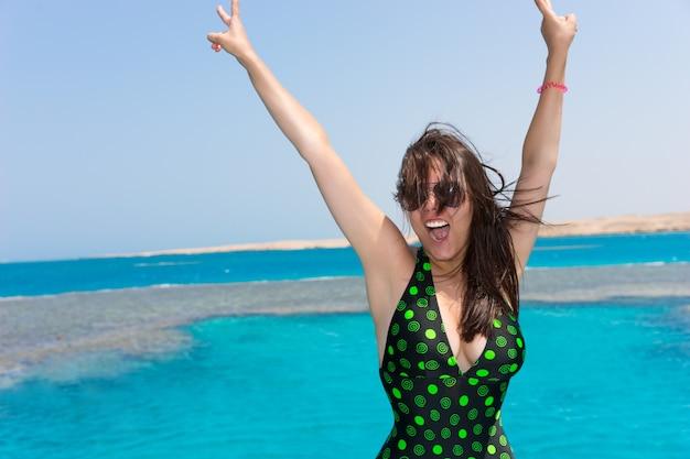 黒緑色の水着を着た女性が手を上げて、晴れた夏の日にヨットで笑い、背景に美しいターコイズブルーの海