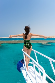 ヨットの鼻の上に立って、晴れた夏の日に手を広げて、そよ風が髪を伸ばし、背景に美しいターコイズブルーの海を背景に黒緑色の水着を着た女性