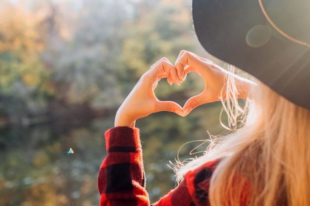 Женщина в черной шляпе делает сердце руками на открытом воздухе