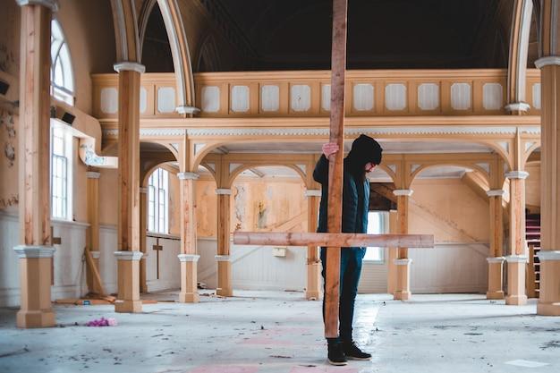 Женщина в черной куртке и черных брюках, стоя на коричневом бетонном здании в дневное время