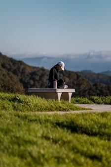昼間に灰色のコンクリートのベンチに座っている黒いジャケットの女性